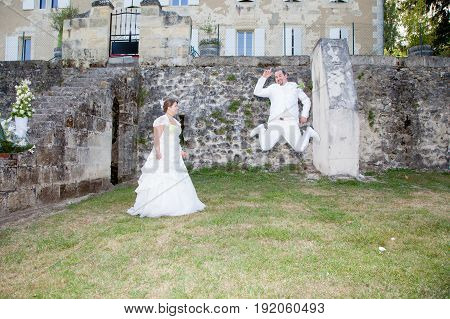 Bride And Groom Jump In Park For Fun
