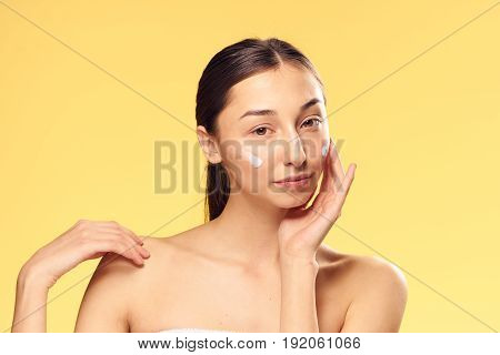 Woman cares for her face, clean skin, woman applied cream on face, woman on yellow background.