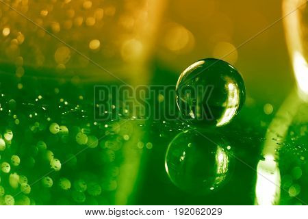 Glass ball on a glass table with reflection on green yellow background. Beautiful bokeh. Art