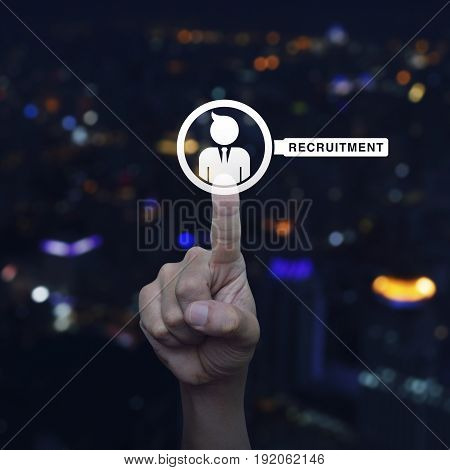 Hand pressing businessman with magnifying glass icon over blur colourful night light city tower Business recruitment concept