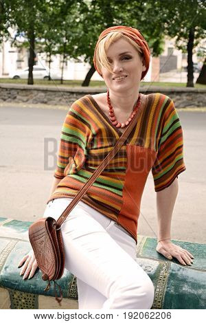 Style of the 1970s. A beautiful long-haired blonde in retro clothes is sitting on a bench in the city: white tights, model hair, high heels, motley accessories, striped blouse