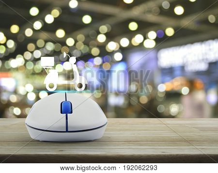 Motor bike icon with wireless computer mouse on wooden table over blur light and shadow of shopping mall Business internet delivery service concept