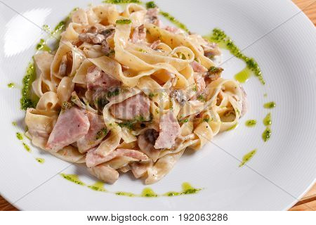 Tagliatelle pasta with ham, mushrooms and yolk. Selective focus. Pasta Carbonara on white plate with parmesan. Italian psta food concept. on a white plate, the dish is served in the restaurant