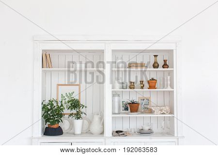 White wooden closet with different decorative items.