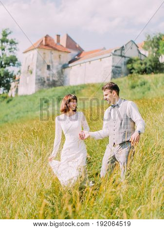 The outdoor portrait of the cheerful newlyweds holding hands and walking in the field near the old castle