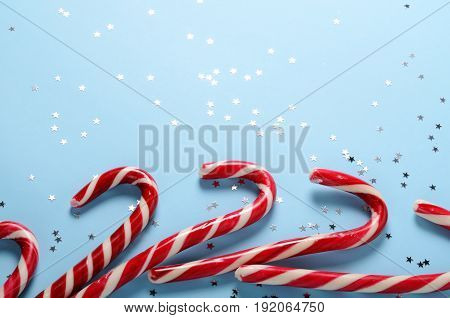 Creative layout made of lollipop cane and sparkling stars.