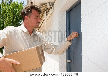 Handsome Delivery Man With Package At Home