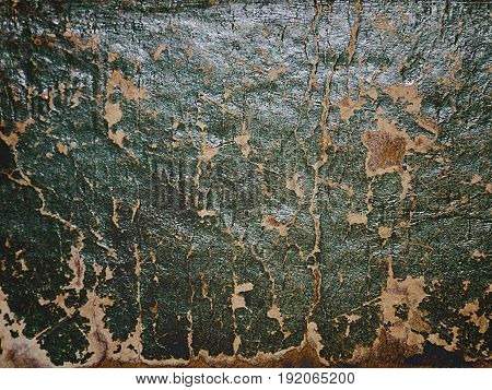 Cracking and peeling green paint on a wall. Vintage wood background with peeling paint. Old board with Irradiated paint