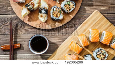 Two sushi sets on wooden plates at table with soy sauce and chopsticks