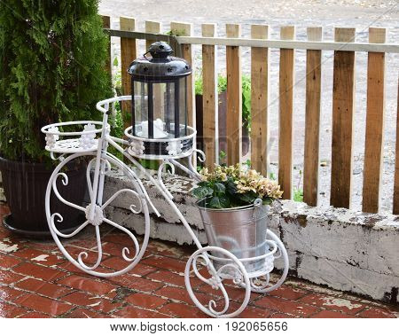White metal pedestal for flower pots and lantern, in the shape of an old tricycle