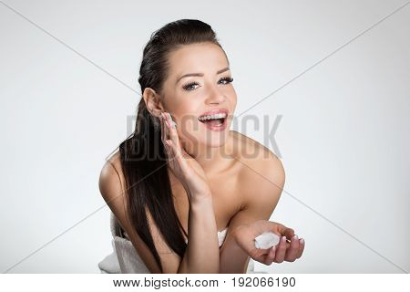 Beautiful Happy Woman Moistening Face With Cream
