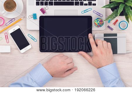 Office desk table workplace with digital tablet pc and mans hands on it. Mens hands work on a tablet. Top view, flat lay business or student concept.