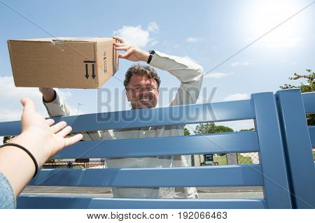 Man Delivery With Parcel At Home In Summer