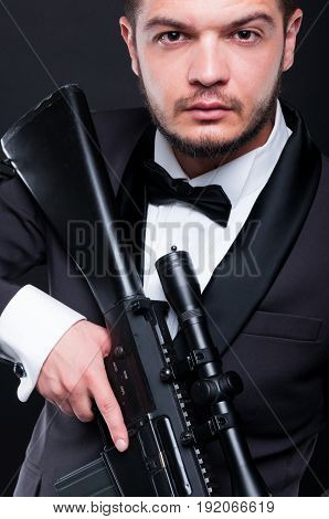 Portrait Of Young Gangster Holding Armed Rifle