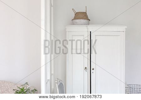 Horizontal indoors shot of white aged closet and chair.