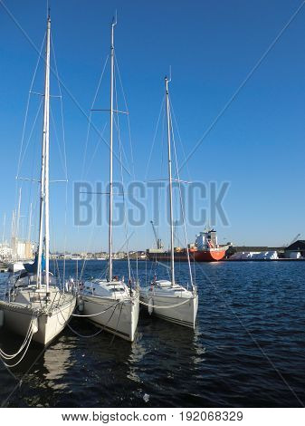 Symmetrical lineup of white sailboats with reflection