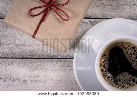 Present box onwooden background. greeting card holidays concept.