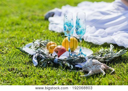 Two blue glasses for champagne on the grass. Wedding accessories.