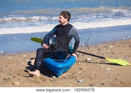 Man with kayak on the beach in sunny day.