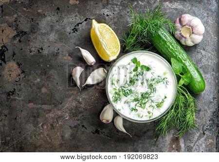 Greek sauce tzatziki with ingredients cucumber garlic dill lemon mint. Food background top view