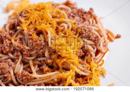 Spaghetti. Italian and Mediterranean cuisine. Spaghetti bolognese with cherry tomato and basil. On a white plate, the dish is served in the restaurant. Italian traditional food