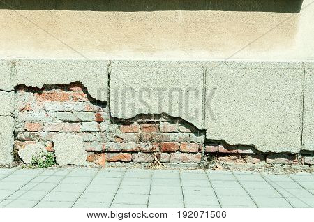 Bad foundations on old house. Cracked house foundations with brick. Street view.