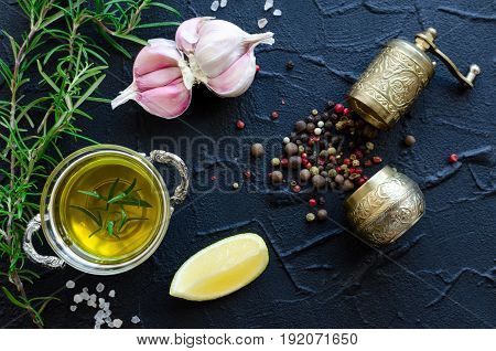 Herbs and spices selection - rosemary garlic lemon salt olive oil and peppercorns with pepper mill on dark stone table. Cooking ingredients concept. Food flat lay. Top view.