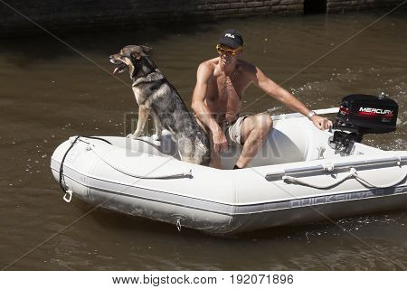 Leeuwarden Netherlands 11 june 2017: tanned man wearing sunglasses rides with his dog in motorized rubber boat on sunny day in summer