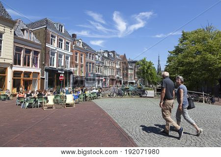leeuwarden 11 june 2017: older couple walks towards outdoor cafe on bridge in the centre of old city leeuwarden in friesland on sunny summer day