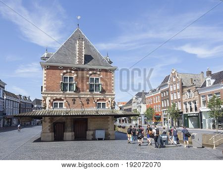 leeuwarden 11 june 2017: group of young people with bags pass waag building on square in centre of leeuwarden in friesland on sunny day