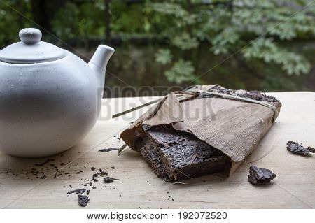 Black natural tea with white teakettle on the wooden table and green leaves as background