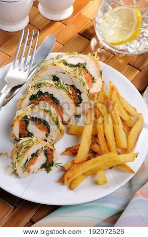 Roll from chicken breast with spinach and carrots under a crust of parmesan dill garnish of french fries