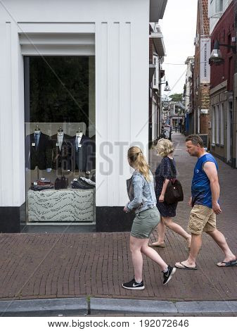 Leeuwarden Netherlands 11 june 2017: man woman and girl pass men's fashion shop in leeuwarden capital of friesland in the netherlands