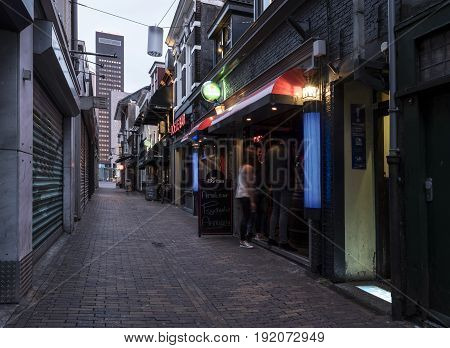 night bar with drinking people in narrow alley in the centre of dutch town leeuwarden in friesland