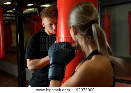 Sexy girl training in a gym in boxing gloves and her boyfriend hiding from her behind a punching bag