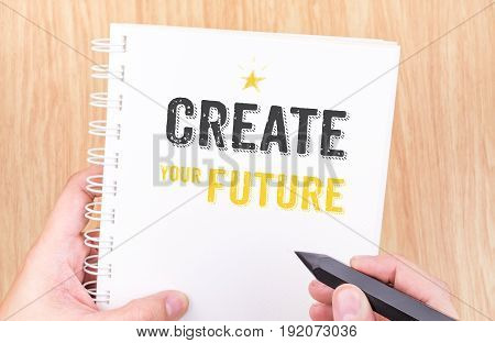 Create Your Future Word On White Ring Binder Notebook With Hand Holding Pencil On Wood Table,busines