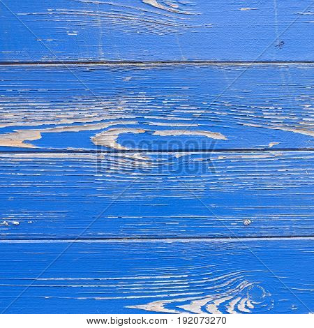 square picture of peeling blue paint texture on hull of old ship in closeup