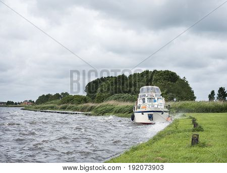 docked yaught on lake near Sneek in dutch province of friesland during summer storm