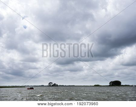 lonely wooden vessel during summer storm on lake near sneek in dutch province of friesland in the netherlands