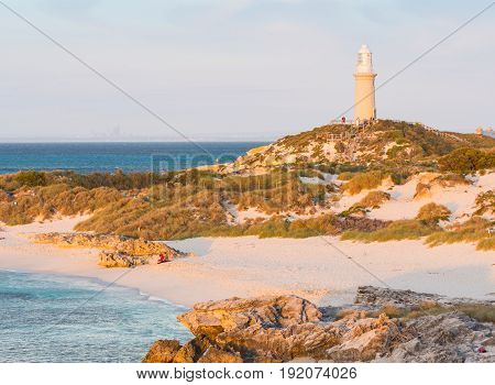 ROTTNEST ISLAND, WESTERN AUSTRALIA - APRIL 16 2017: Tourists enjoying the golden hour at Pinky Beach and Bathurst Lighthouse on Rottnest Island near Perth in Western Australia.