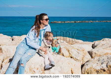 Back view of mother and her little daughter looking at the sea