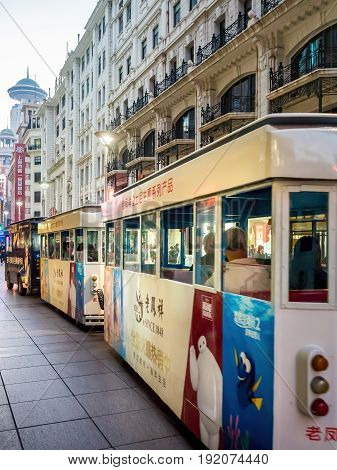 Shanghai, China - Nov 4, 2016: Along Nanjing Road Pedestrian Street - Buildings in western architectural designs. Sightseeing train on the street.