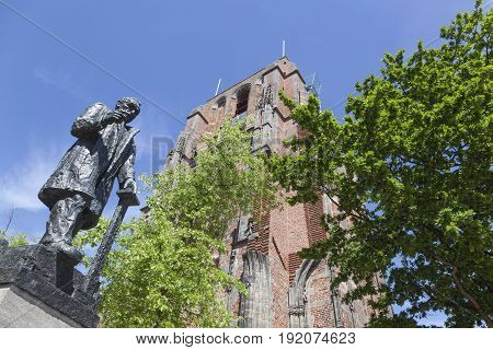 statue of troelstra next to oldehove tower in the centre of leeuwarden capital of friesland in the netherlands with blue sky