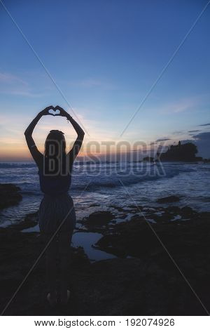 Girl holding a heart shape on the ocean / sea shore.