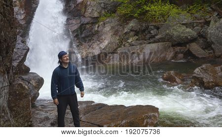 Man Standing in front of Glen Ellis Falls at Pinkham Notch in New Hampshire