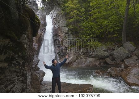 Man Standing in praise in front of Glen Ellis Falls at Pinkham Notch in New Hampshire