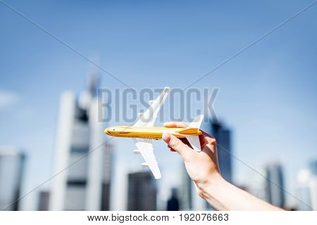 Holding a toy airplane on Frankfurt cityscape background. Frankfurt has a very large airline connection in Europe