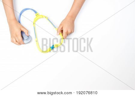 Top view on child's hands with toy stethoscope on a white background. Copy space for text