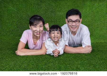 Happy Asian Chinese Parents And Daughter Lying On The Grass