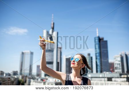 Young woman playing with toy airplane on the modern cityscape background in Frankfurt. Air transportation concept in Frankfurt. Frankfurt has a very large airline connection in Europe